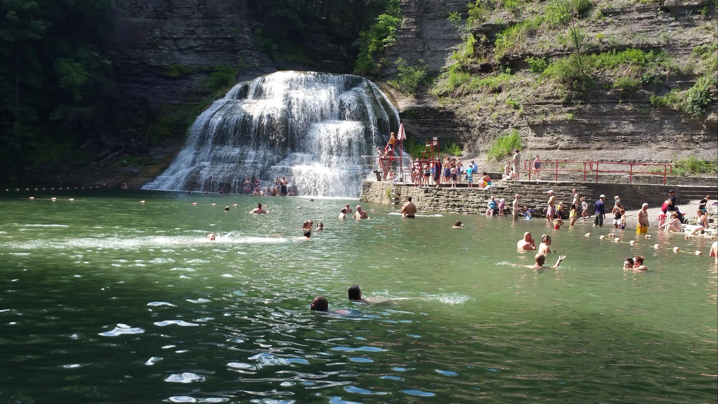 waterfall with people swimming