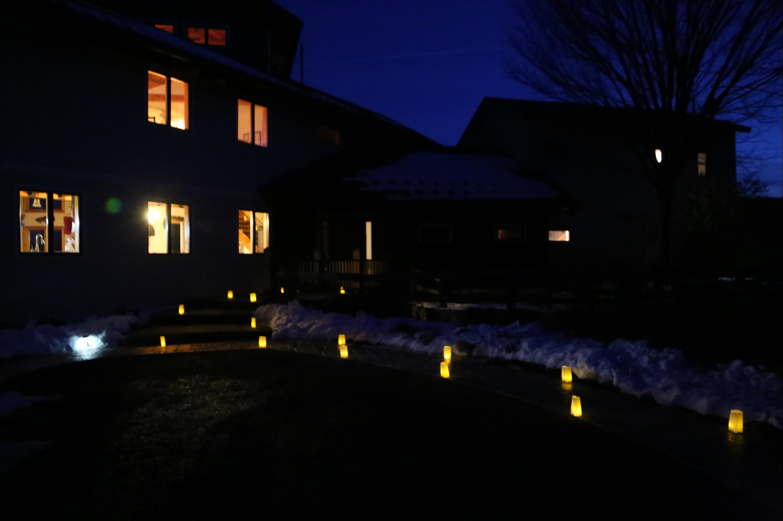luminaries approaching house at dusk